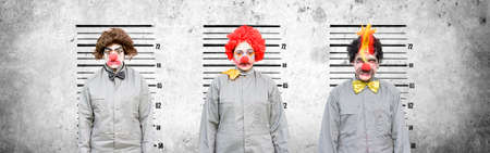 line up: A Male And Two Female Clowns Who Face Criminal Charges Lineup Against A Cement Wall In An Attempt To Find Out The Criminal Amongst The Thugs In A Line Up Of The Usual Suspects