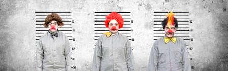 Eine männliche und zwei weibliche Clowns, die in einem Versuch Strafanzeigen Lineup gegen Wand Zement Angesicht zu Angesicht den Verbrecher der üblichen Verdächtigen in einem Line-Up Amongst The Thugs finden Standard-Bild