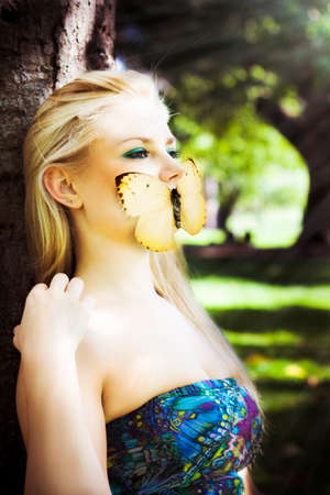 silenced: Gorgeous Blonde Woman Silenced By A Butterfly Over Her Mouth While Sitting Against A Tree In A Enchanted Forest, Image Titled Beauty In Silence Stock Photo