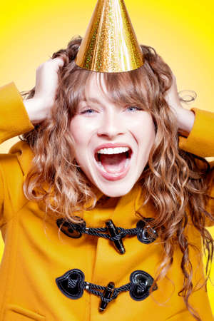 merriment: Crazy and overjoyed party girl in a gold party hat laughing in merriment as she runs her hands through her wavy blonde hair Stock Photo