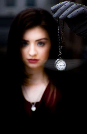 foreground focus: Portrait Of Hypnotised Young Woman With Gloved Hand And Stopwatch In Focus In Foreground Stock Photo