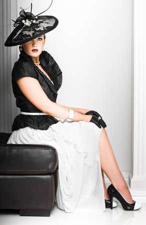 sombrero: Señora con clase en un elegante conjunto de la alta costura con un sombrero de fascinator y accesorios sentada recatadamente en un asiento con la postura erecta
