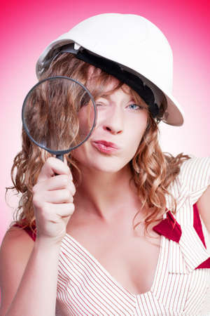 Attractive female building inspector wearing a hardhat while holding a large magnifying glass as she goes about her work expecting quality on the building site, conceptual studio portrait