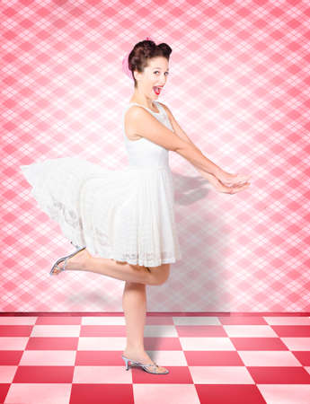 motioning: Creative portrait of an attractive pinup woman with expression of surprise running at speed in vintage kitchen with motioning white dress. Retro rush