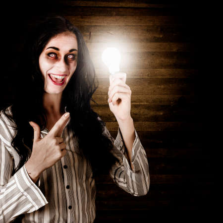 ghoulish: Zombie business person standing in a dimly lit attic holding an illuminated lightbulb in a depiction of a bad idea