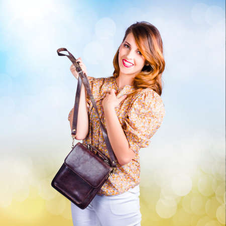 straps: Cute young retro fashion model holding leather clutch bag with hand to chest. Love of retro fashion accessorys Stock Photo