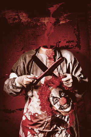 boogie: Disturbed evil clown surgeon holding surgical scissors while laughing with decapitated head in hand. Headless boogieman