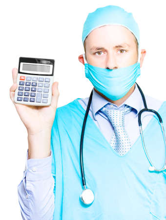 health answers: A male doctor in a gown and mask with a stethoscope around his neck holds up a calculator, conceptual of the increasing cost of healthcare