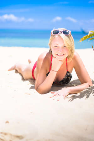 sandy beach: Woman Lying Face Down On A Sandy Seashore With Sunglasses On Head And A Big Toothy Smile In A Expression Of A Happy And Relaxing Holiday Break