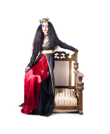 regal: Queen with crown sitting on wooden throne chair, white studio background