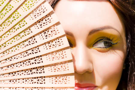 impish: A Beautiful Mischievous Woman Wearing Yellow Eyeliner Makeup Hides With A Sly And Sneaky Smirk Behind A Wooden Hand Fan In A Playful Fun In The Sun Image Stock Photo