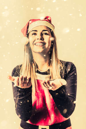 living moment: Antique photo of a beautiful vintage girl in santa hat playing outside in falling snow flakes. To celebrate a white christmas