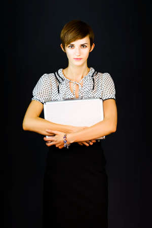 clutches: Pretty young woman on a dark background looks at the camera with trepidation as she clutches a briefcase to her chest in a new employee concept