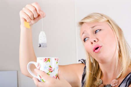 relieved: Relieved Woman holding tea bag and mug in office kitchen in a morning tea break concept