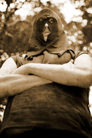 deranged: Sepia Toned Big Bellied Vintage Hitman Standing Arms Crossed Stock Photo