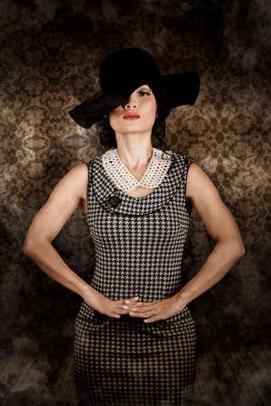 moda ropa: Retrato de un modelo asiático joven y atractiva con un vestido de moda de la vendimia con el sombrero negro y perlas collar de disquete Foto de archivo