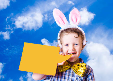 easter message: Cute Boy Wearing Bunny Ears Announcing Happy Easter Message Through A Empty Speech Sign