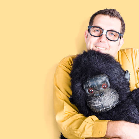 dweeb: Big goofy man cuddling soft toy gorilla on yellow background. Comfort zone concept