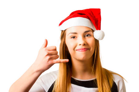 Isolated photo of a woman in santa hat making phone hand gesture. Christmas service hotline