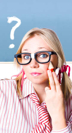 enquire: Sweet young blonde girl in geeky glasses with large pencil to face inquiring for an answer to a big question. Chalk board background Stock Photo