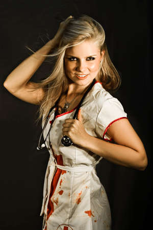 Dead Sexy Nurse Standing Wearing Blood Stained Nurses Uniform In The Dark Shadows Of A Gore Hospital Ready For The Next Amputation Stock Photo