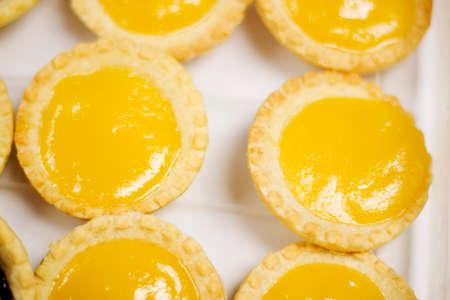 lemony: Bright Yellow Lemon Tarts Sit On A Kitchen Baking Tray