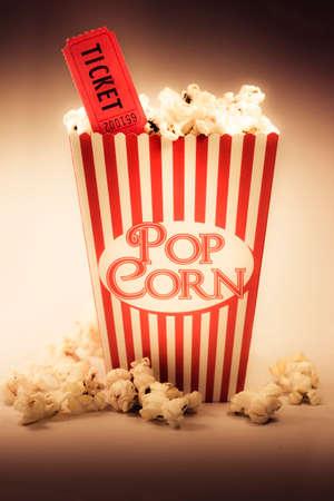 palomitas: Representación de los años cincuenta cine era con una rayada roja de la vendimia vieja caja de palomitas de maíz que desborda con palomitas de maíz con mantequilla, junto con un boleto de la película
