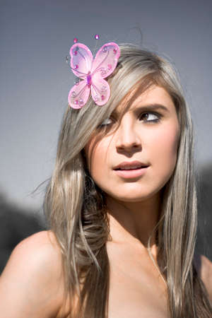 hairclip: A Sexy Lady Stands Outdoor Accessorizing With A Pink Butterfly Hair Clip On Her Head In A Connection Back To The Environment With A Touch Of Nature