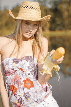 hostility: Corn Cob Cowgirl Pulls Out A Corncob And Takes Aim To Shoot With A Snarling Expression Of Outback Hostility Stock Photo