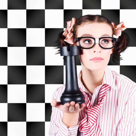 brainy: A pretty brainy nerdy young woman in glasses holds an outsize chess piece in her hand against a black and white chessboard backdrop advocating intelligent marketing with prior planning and strategy