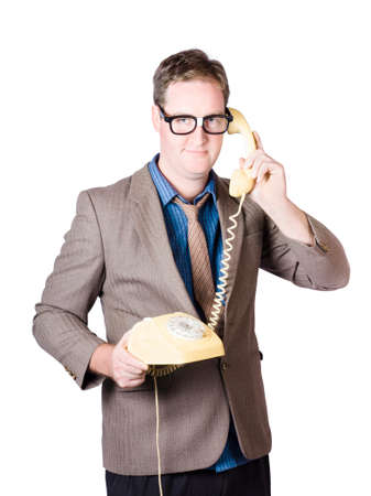 olden day: Comical businessman holding corporate talk when dialling in on a 1950s yellow retro telephone Stock Photo