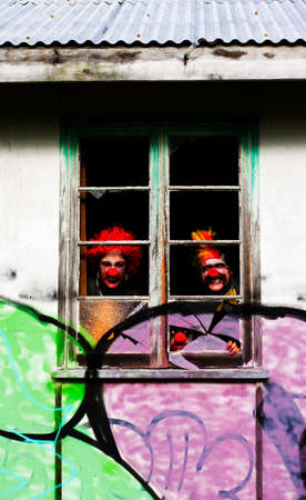 ghoulish: 3 Ghoulish Clowns Stare Peering Out Of The Darkness Inside The Haunted House Of Horrors Stock Photo