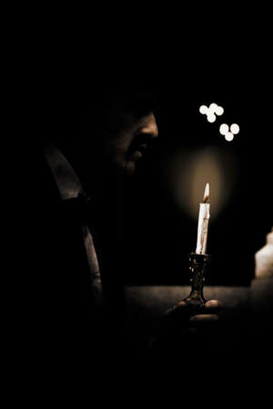 guiding light: Man Uses A Candle As His Guiding Light To Illuminate The Darkness When Walking Through The Unknown Eerie Dark Passageways And Secret Opens To His Future Stock Photo
