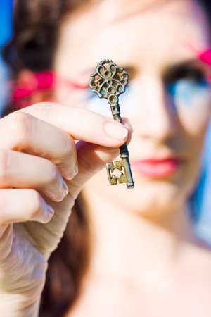 skeleton key: Retro Woman Holds Up A Vintage Skeleton Key During A Keys Handover For A Home Or House In A Real Estate Sold Concept