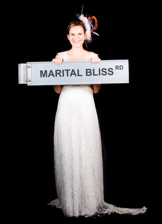 marital: Happy Bride Holding Street Sign In A Concept Of The Saying On The Road To Marital Bliss