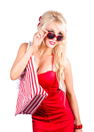 over the shoulder: Attractive blond woman in red dress and sunglasses with shopping bag over shoulder