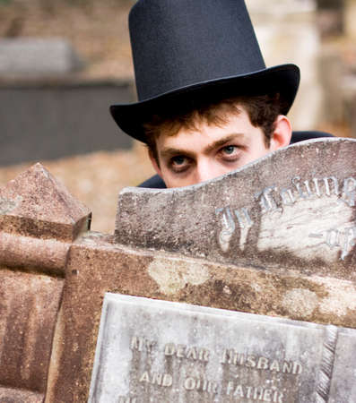 cemetery: Man Plays Peek A Boo While Hiding Behind A Cemetery Tomb Stone