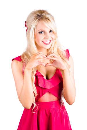 haciendo el amor: Una mujer rubia haciendo una forma de corazón con sus manos Foto de archivo