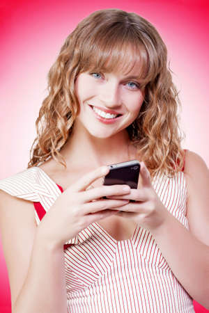 fulfilment: Beautiful young woman with a lovely gentle smile texting on her mobile phone against a red studio background with gradient colour