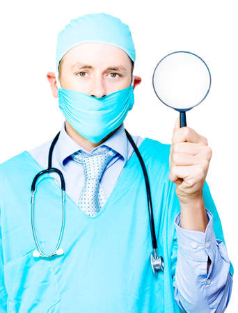 scrutinise: Doctor in gown and mask holding a magnifying glass in his hand conceptual of undergoing a medical examination and investigation
