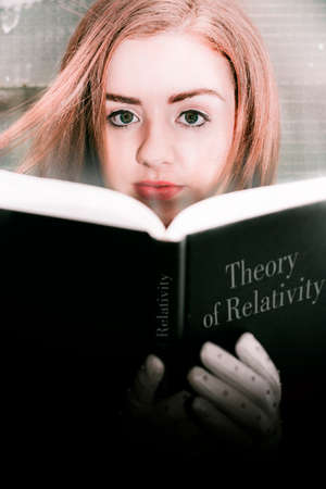 the theory of relativity: Young Woman Holding An Open Book On Einsteins Theory Of Relativity In Front Of Her, Looking Over The Top At The Viewer