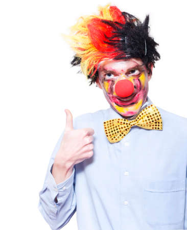 quirky: Quirky Circus Clown Performer Pointing Up To Blank Carnival Advertising Space Over White Background