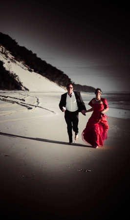 motioning: Happiness Fills The Strides Of A Bride And Groom Running Down The Beach In A Beach Wedding Romance