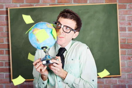 dweeb: Nerdy business man holding earth world globe in school classroom when developing a plan for global expansion Stock Photo