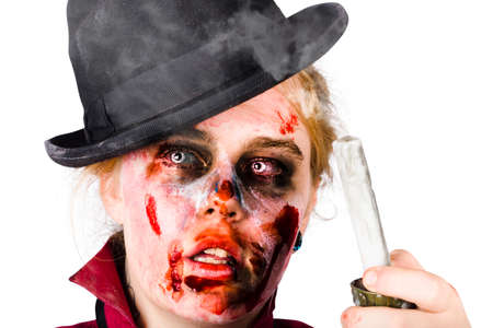 life after death: Fearful zombie woman with facial cuts and bruising wearing bowler hat holding an smouldering wax candle while on a scary ghost hunt. Stock Photo