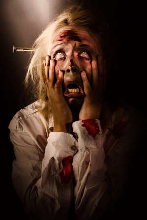 horror: Dark horror portrait of a dying bloody zombie griping face with hands in fear and terror while looking up to the light. A passing scream between heaven and hell