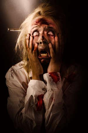 infierno: retrato oscuro horror de una cara griping zombie sangrienta morir con las manos en el miedo y el terror mientras mira hacia arriba a la luz. Un grito que pasa entre el cielo y el infierno