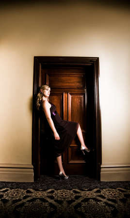 locked: Glamorous woman in evening wear blocking access to a closed wooden doorway with her elegantly raised foot in a no escape and no entry concept