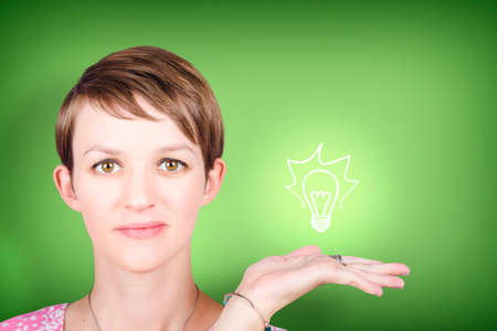 green environment: Woman showing illuminated light bulb on green background. Environment and ecology idea concept