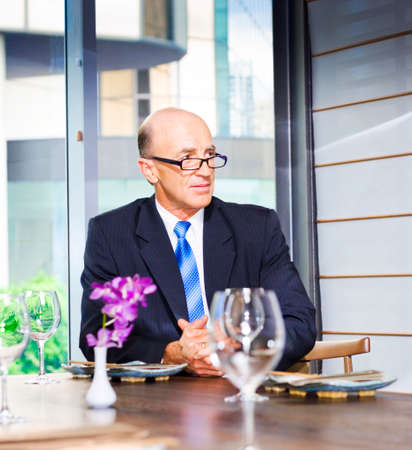 functions: Senior Business Executive Attending Function. A senior businessman seated at a table with wineglasses looking away from camera, corporate environment.